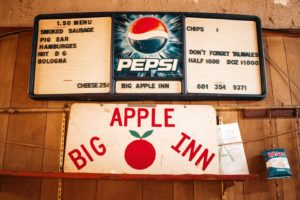 A hand-painted red and white Big Apple Inn sign with a red apple. Above a menu board displays pig ear sandwiches for $1.50