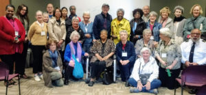 Elizabeth Eckford sitting in a wheel chair surrounded by a large group of travelers who just enjoyed a talk with her.
