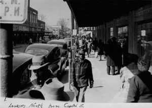 Black and white photo of people walking down the sidewalk next to businesses on Farish street in the 1940s
