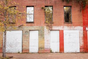 Boarded up windows and doors of a red brick building on Farish Street - Jackson, Mississippi