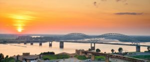 View from HU Hotel in Memphis, TN of the bridge crossing the Mississippi River with a beautiful orange sunset in the background