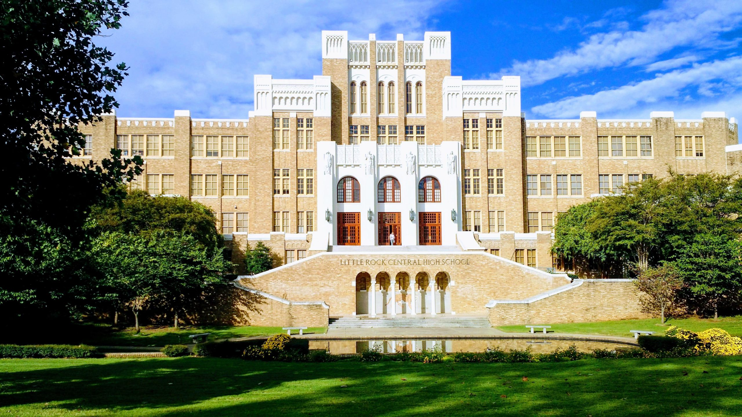 Tan facade of the three story Little Rock Central High School with large white columns framing the three entrance doors.