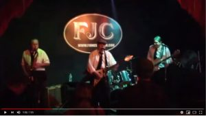 Video still of Sherman Lee Dillon and two other band members all in white shirts and black ties at the Frank Jones Corner