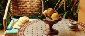Villa Mandarine-Rabat, Morocco. A tiled round table, bowl of fruit, and wicker chair with teal cushion on room's terrace