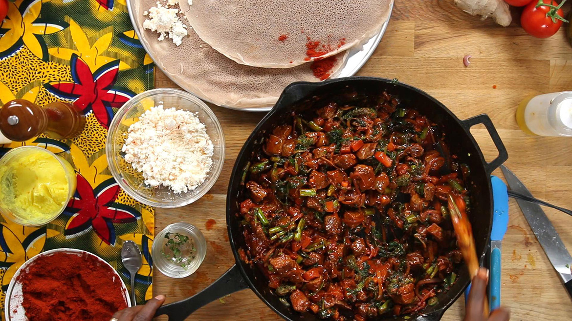 Unseen Chef Marcus Samuelsson stirs beef tenderloin, broccoli, and tomatoes in a cast iron pan for the Ethiopian dish Tibs