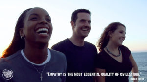 """Three smiling college students with Roger Ebert's quote """"Empathy is the most essential quality of civilization"""""""
