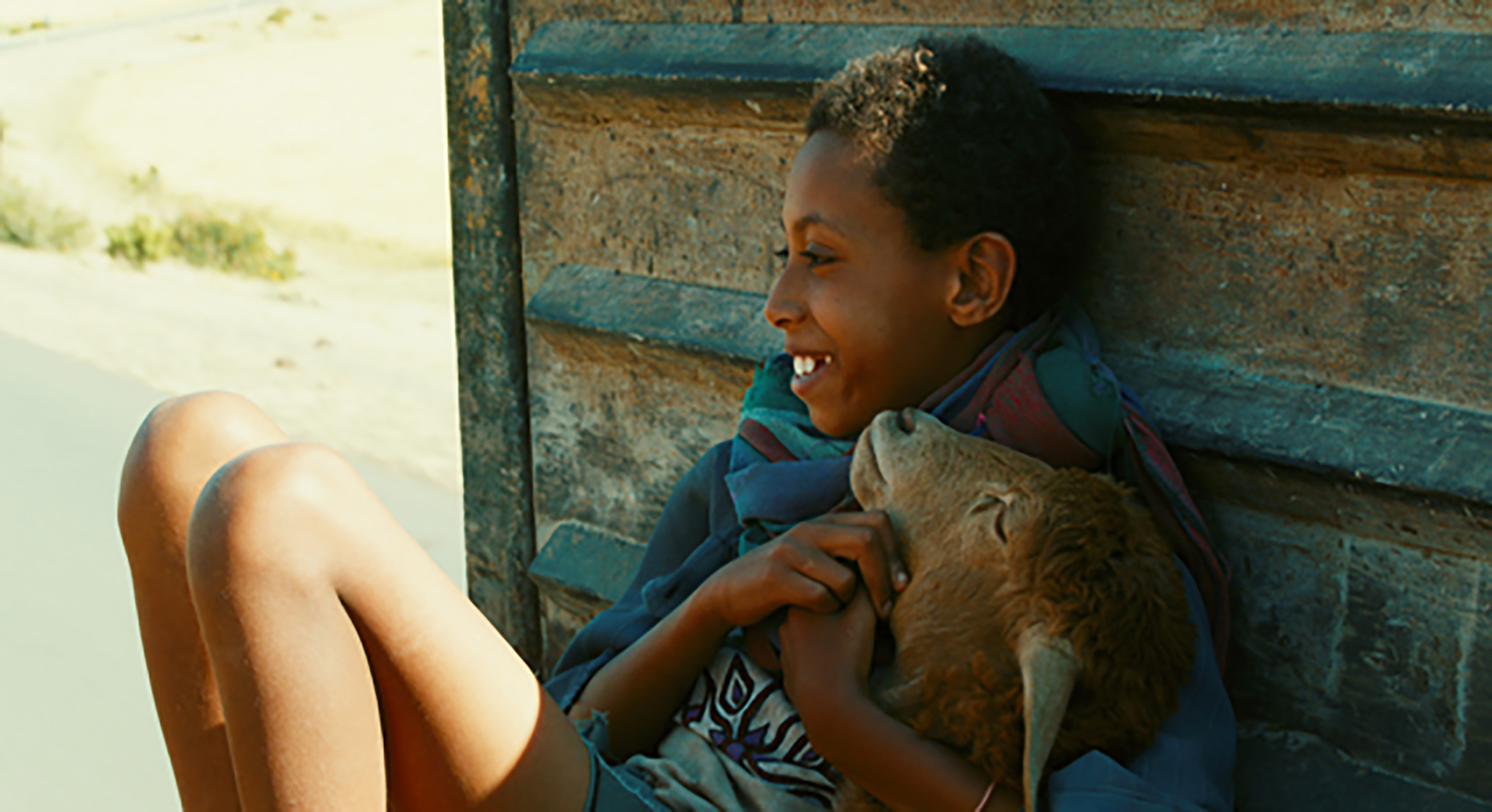 Movie Lamb Small Ethiopian boy sitting against a wall with his knees up cuddling his rust colored sheep and smiling