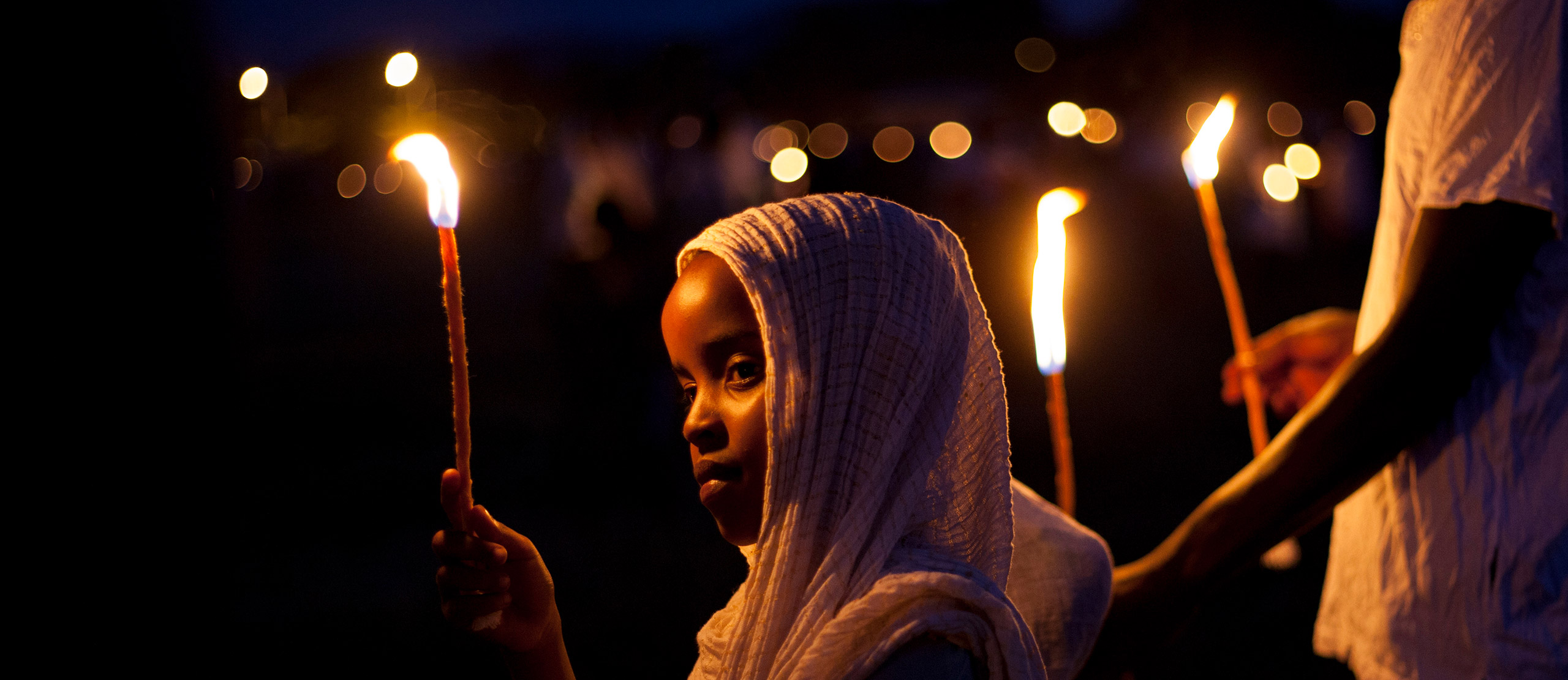 A young Ethiopian clothed in white carries a long lit candle during a silent evening religious ceremony.