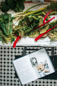 Preparations for Zelnik Pie with the cookbook splayed open on a black bar stool next to a table of leafy green ingredients