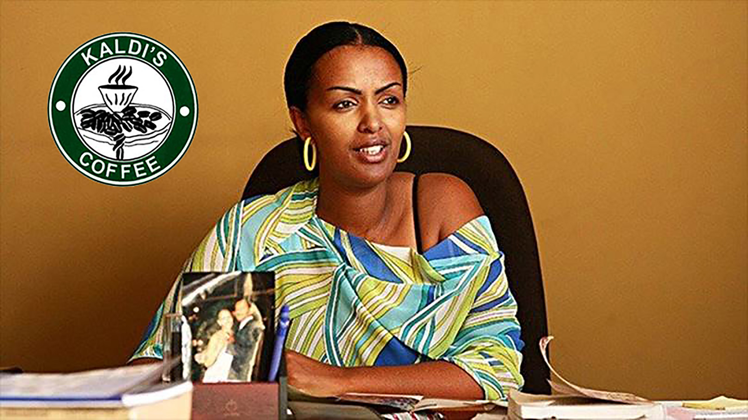 Tseday Asrat, founder of Kaldi's Coffee, Ethiopia's largest coffee shop chain, sitting at a desk with company logo behind her