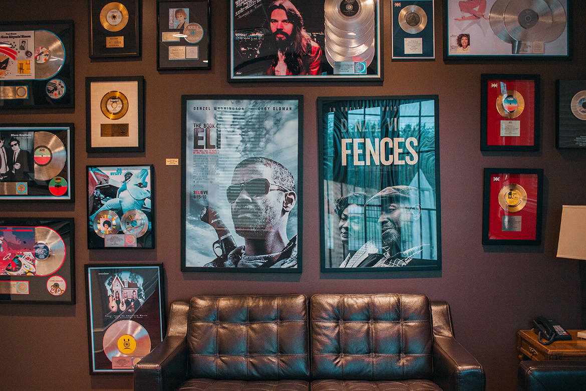 Photo of a wall inside of Malaco records recording studio. The wall displays various artists photos, silver or gold records, and movie posters.