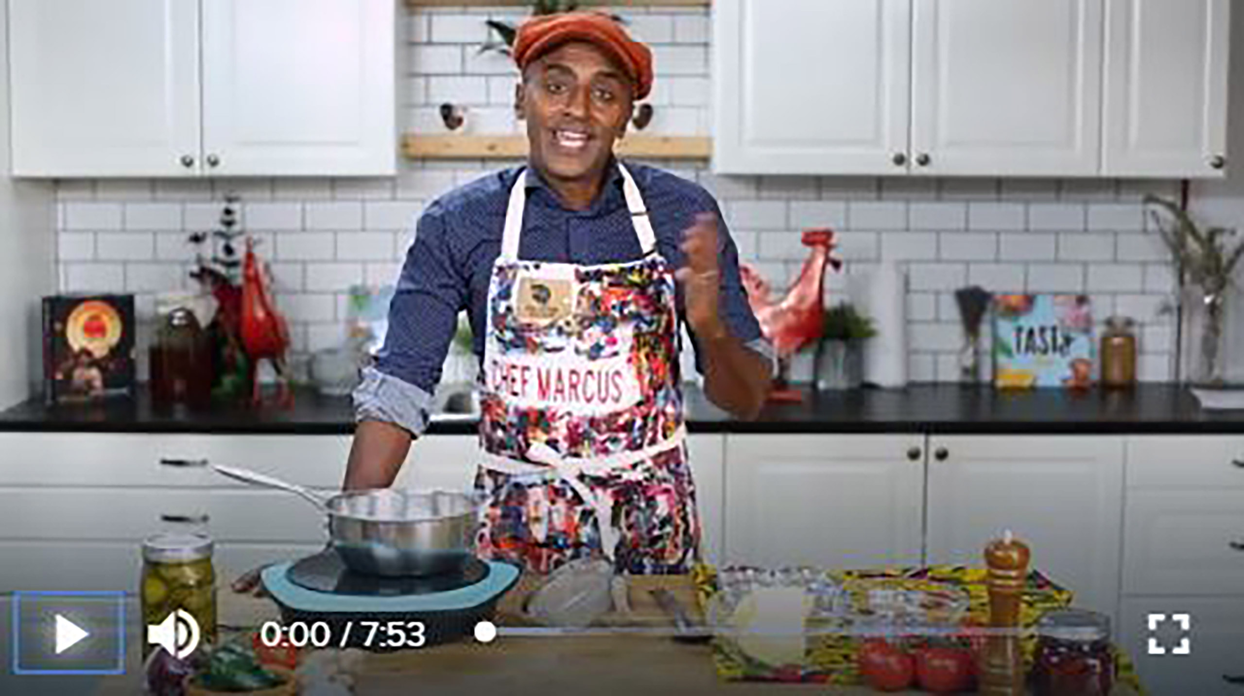 Chef Marcus Samuelsson with apron and red cap in his kitchen demonstrating how to make the Ethiopian dish, tibs