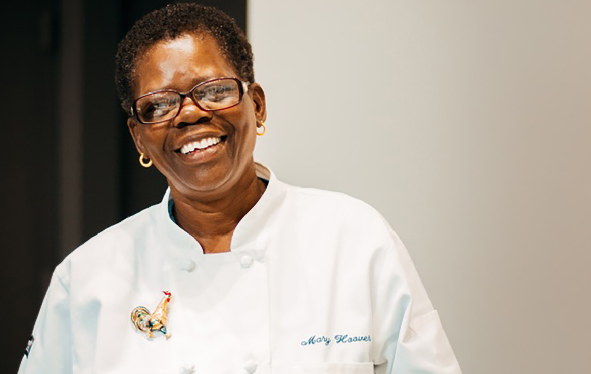 A smiling Mary Hoover in her chef jacket getting ready to share her secret behind her delicious ribs