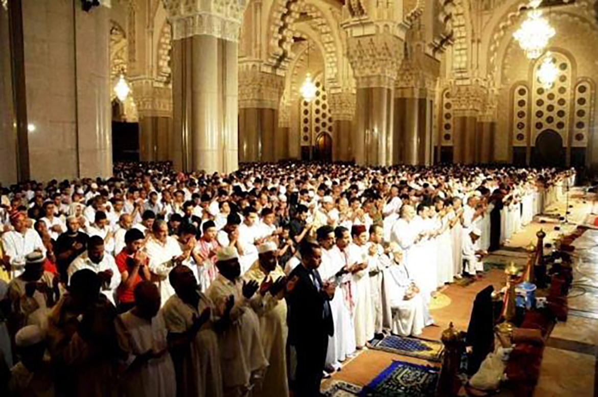 Hundreds of men mostly clothed in white robes prepare for nightly prayers in a beautiful huge mosque for Ramadan in Morocco.