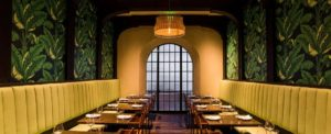 Aziza's long dining space. A long padded backseat lines each green leaf wallpapered wall leading to a large oval window