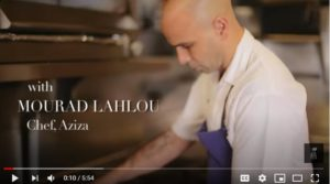 Video still of Chef Mourad Lahlou's in a kitchen with a white short sleeved shirt and blue apron making a tagine recipe