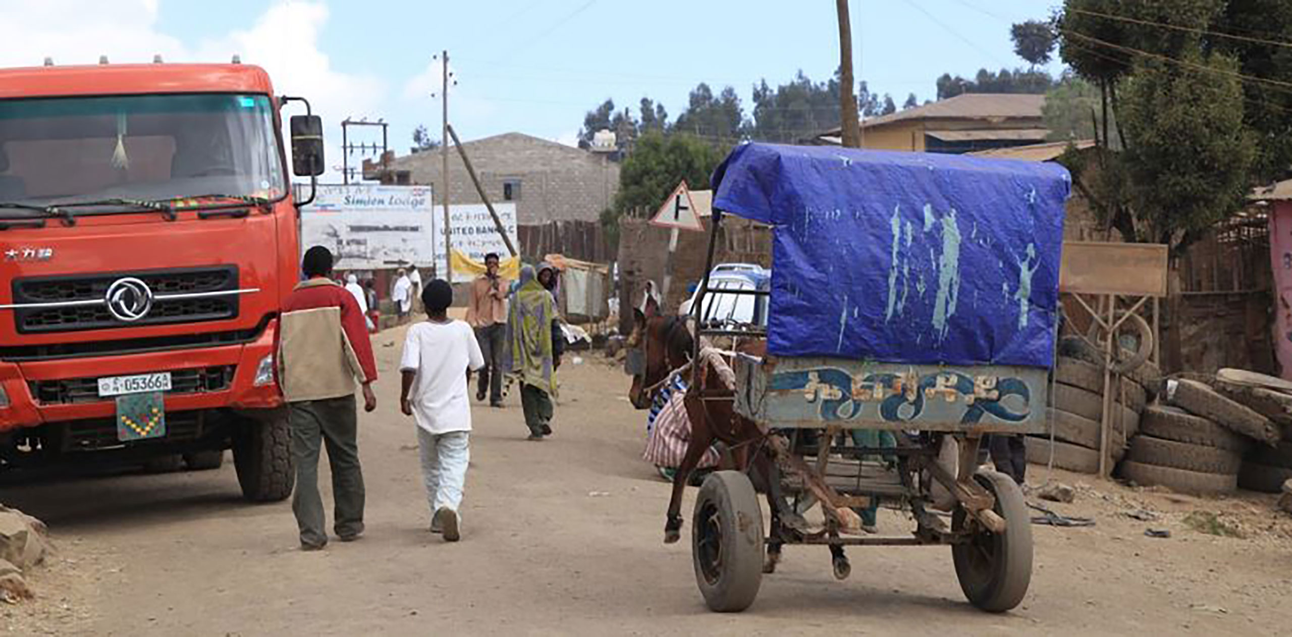 Ethiopians walking around at a truck stop in Debark, Ethiopia. A large red semi dwarfs a nearby horse-drawn carriage