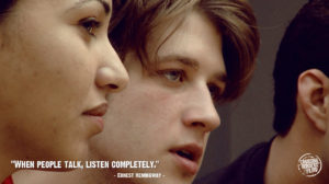 """Close up of one male and one female college student with Ernest Hemingway's quote """"When people talk, listen completely"""""""