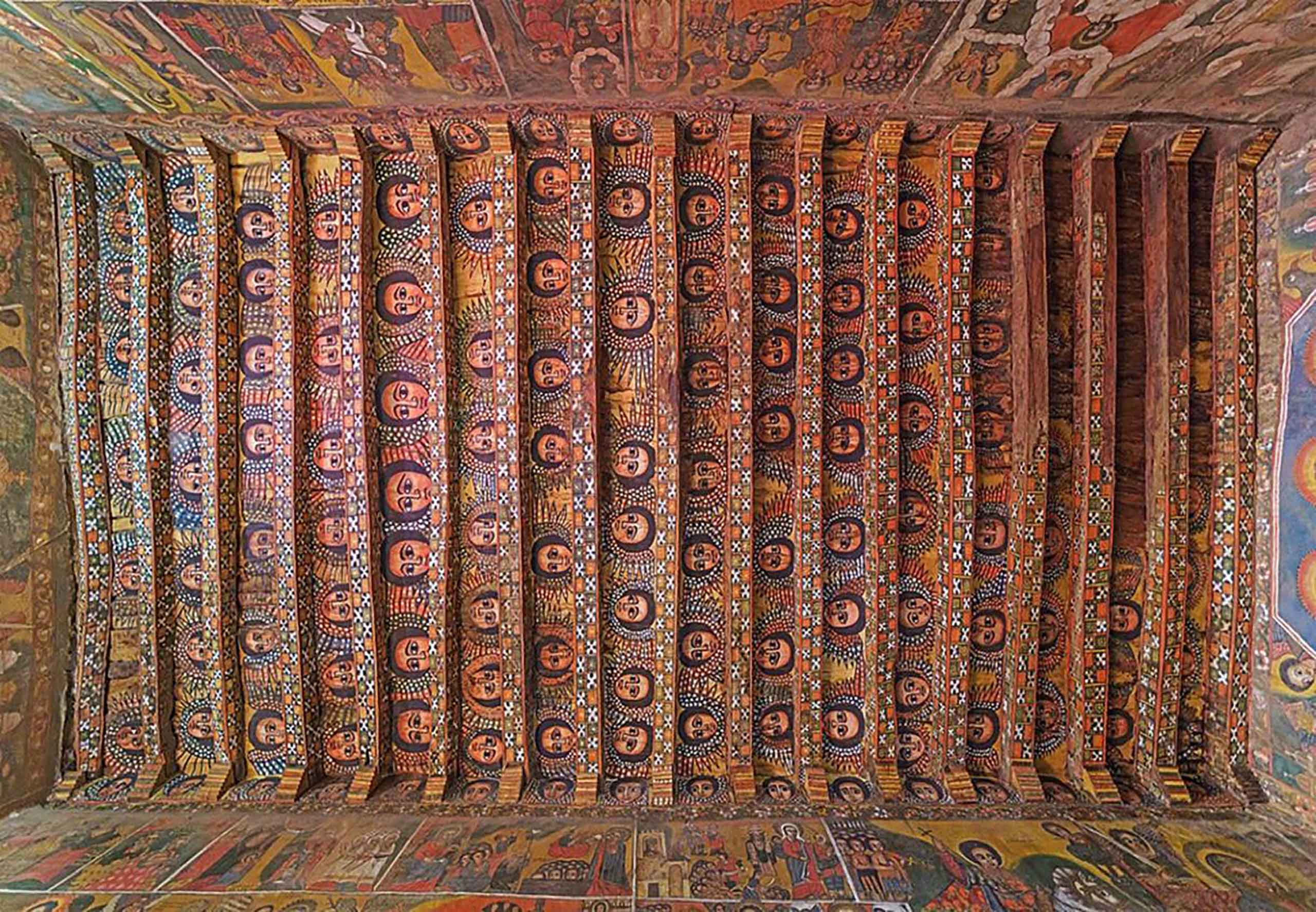 Painted angel faces in rich red, blue and golden hues on the ceiling of the Debre Berhan Selassie Church in Gondar, Ethiopia.