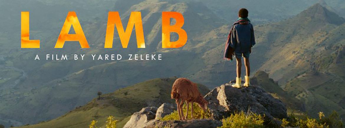 Movie Lamb by Yared Zeleke. Young boy in a cloak shorts boots with a rust colored lamb gazing over the green hills of Ethiopia