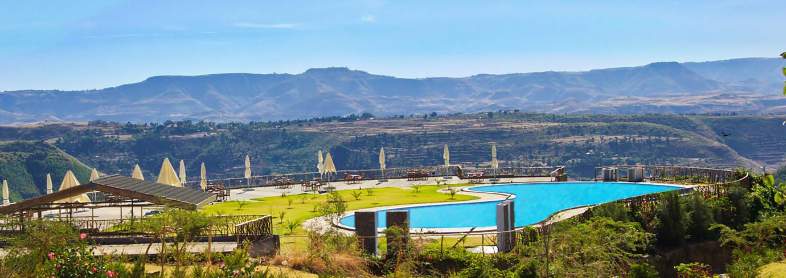 Vast grounds of the Gondar Hills Hotel with a sizeable blue pool, surrounded by the beautiful hills of Gondar, Ethiopia.