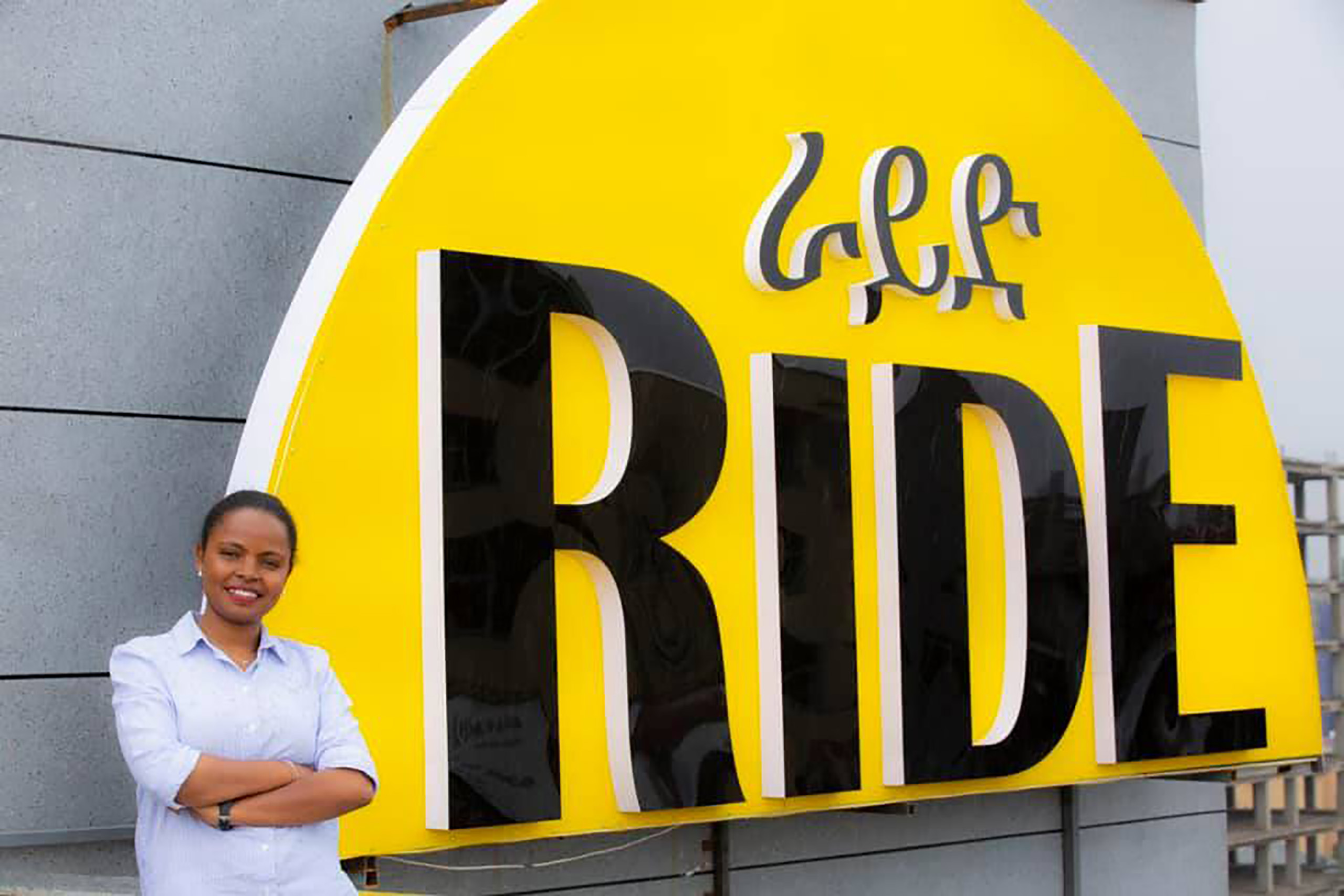 Samrawit Fikru, creator of RIDE app, smiling next to a large yellow and black semi-circle RIDE sign in Addis Ababa, Ethiopia