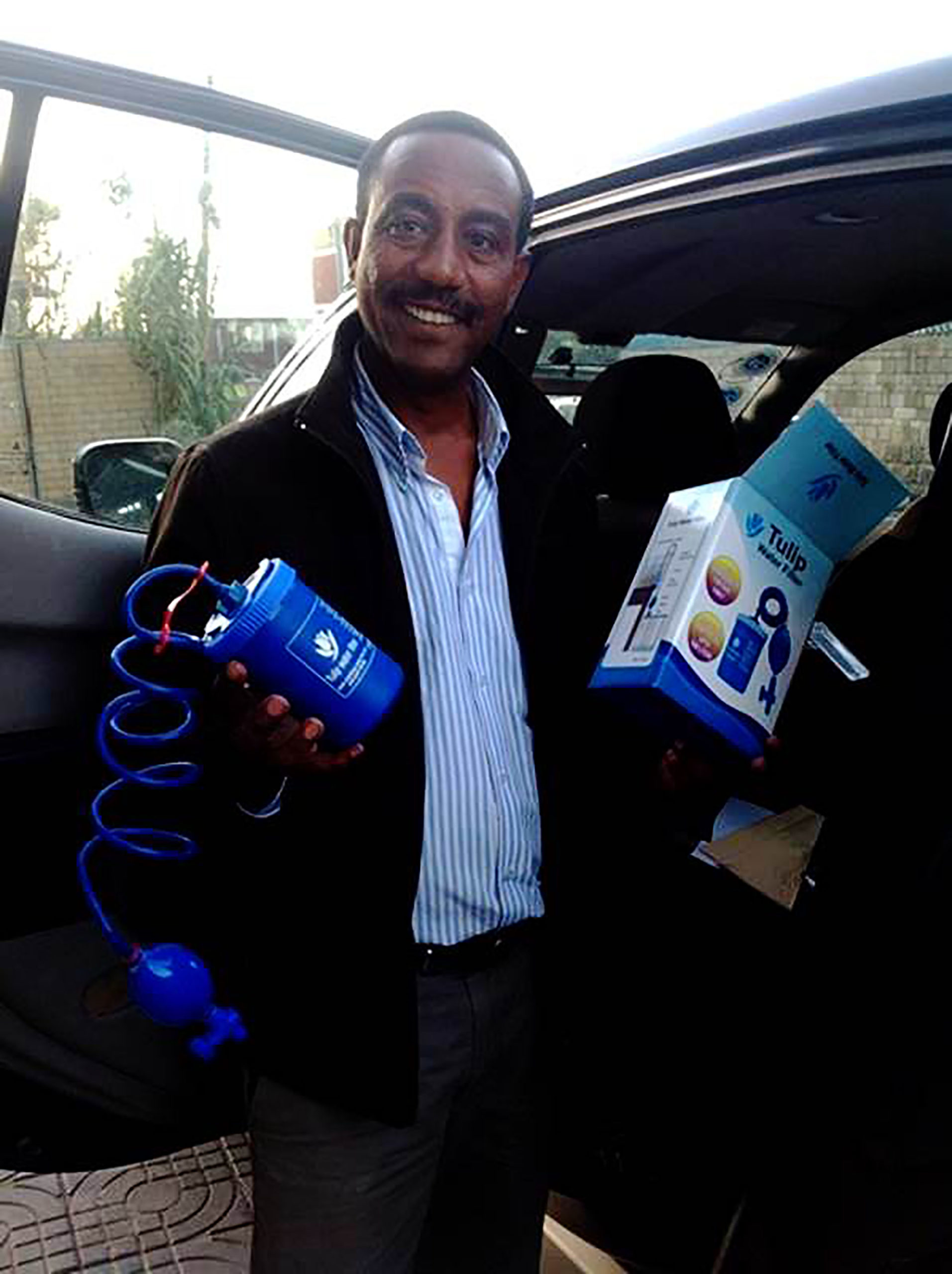 Getaw Mekonnen Cherinet founder of Tulip Addis Water Filter, standing by a car holding his ceramic water filters in Ethiopia