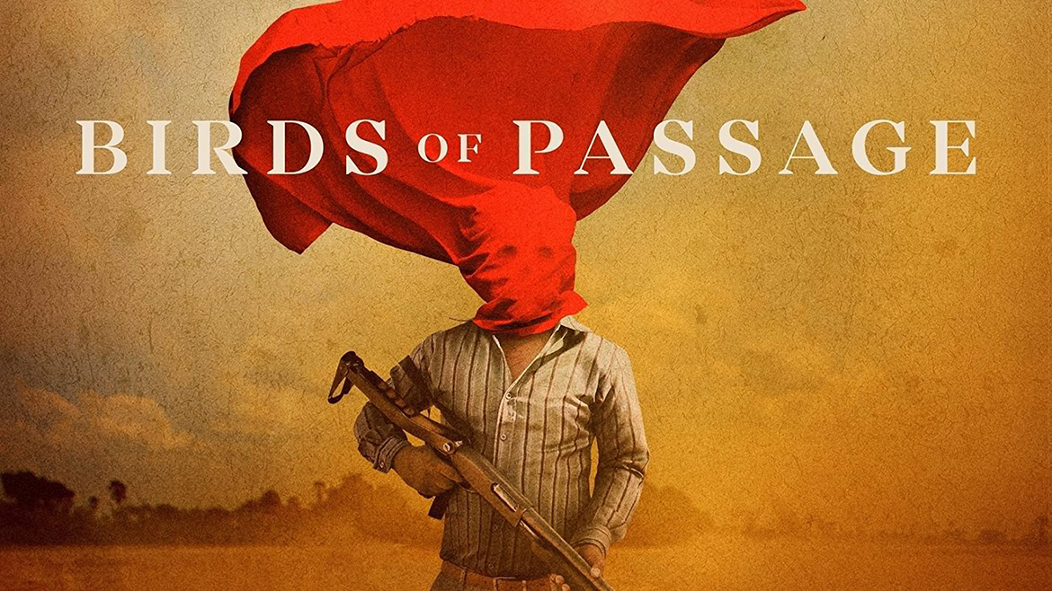 Birds of Passage film poster. Man holding automatic gun stands in a dusty field. A red sheet covering his face blows behind