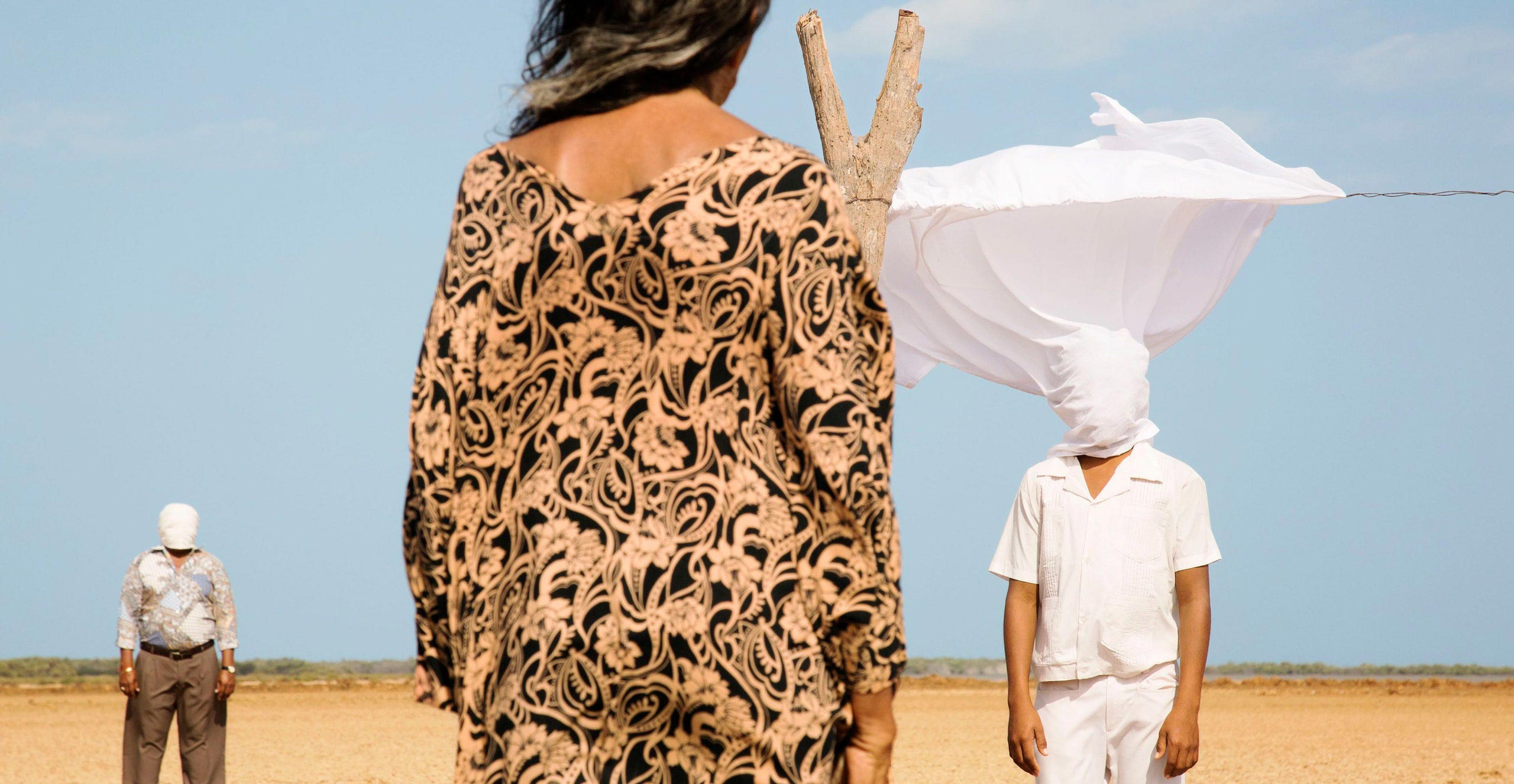 The back of a women facing two men in the desert with white sheets over their faces