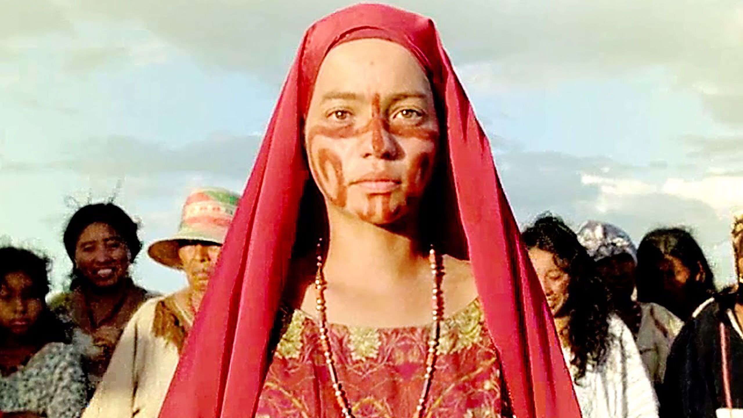 Zaida, a young women from Wayuu tribe dressed in red with a tribal design painted on her face in brown.