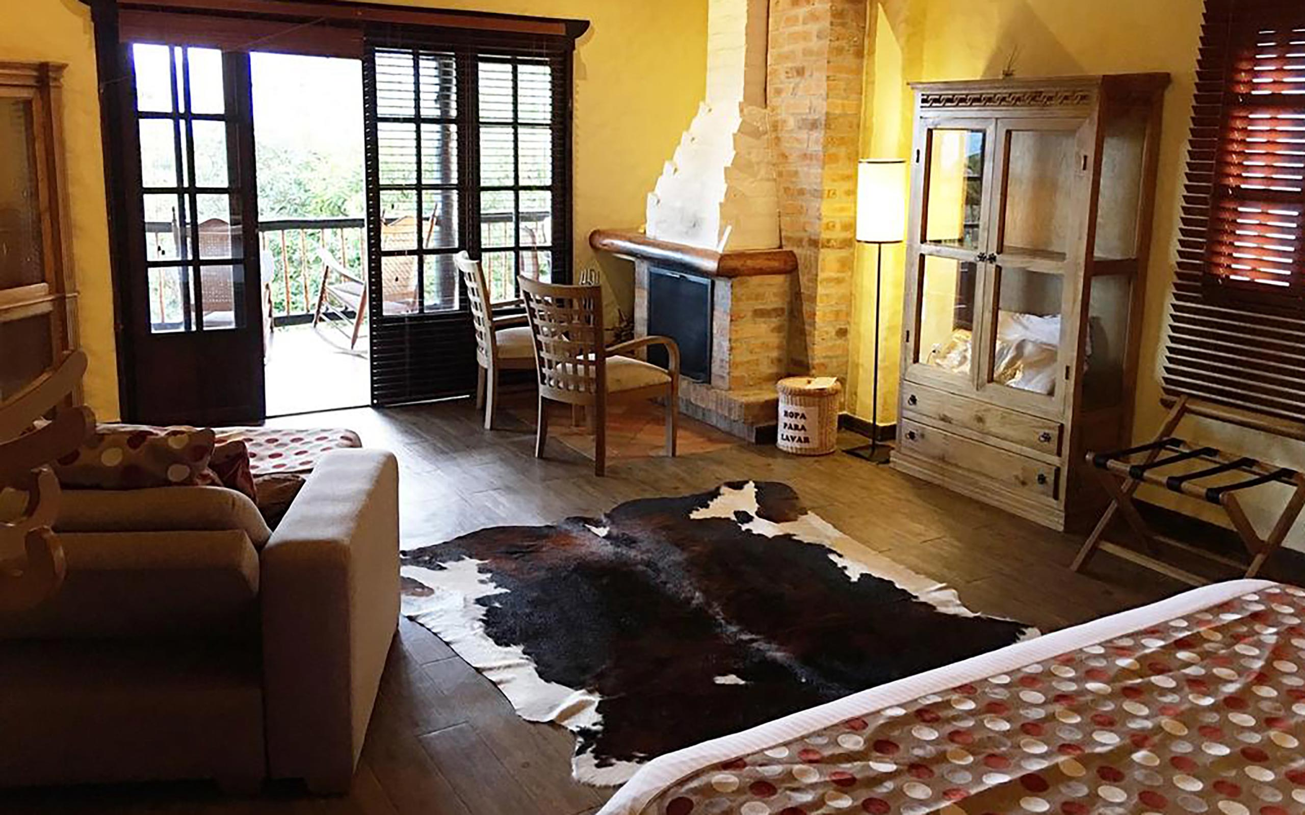 A guest room at hotel Monasterio with a brick fire place, wood armoire, on the floor an animal skinned rug, and a brown chair