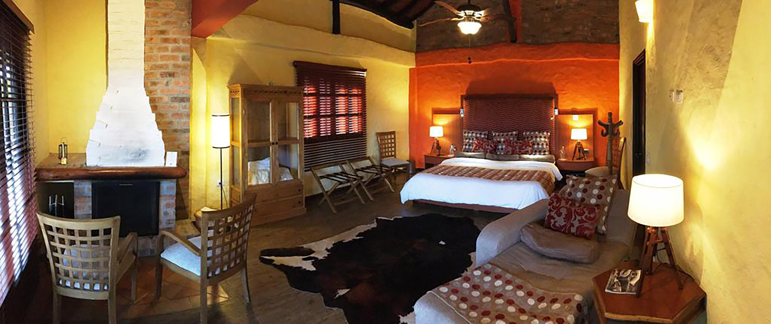 A guest room a hotel Monasterio with a brick fire place, wood armoire, an animal skinned rug, large bed, and a brown chair