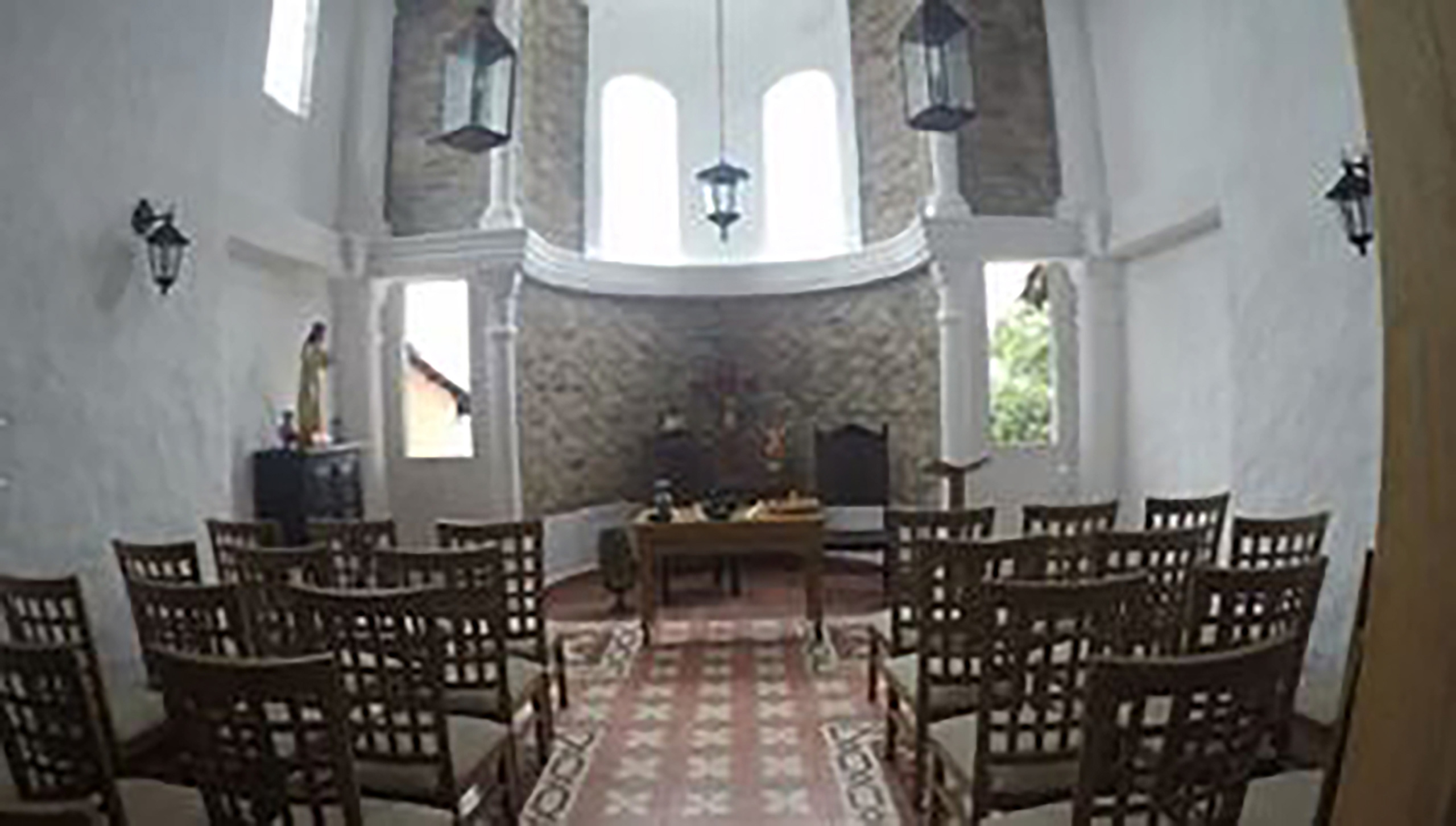 A chapel in a long skinny room with chairs. At the front of the room is a table with objects on them and a statue of Jesus