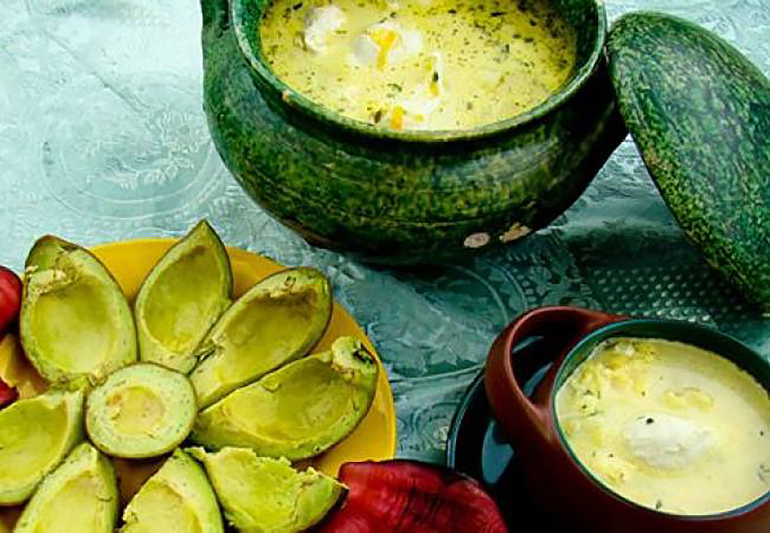 A plate with slices avocados all around it and a bowl of a Colombian soup with yellow coloring in a green bowl