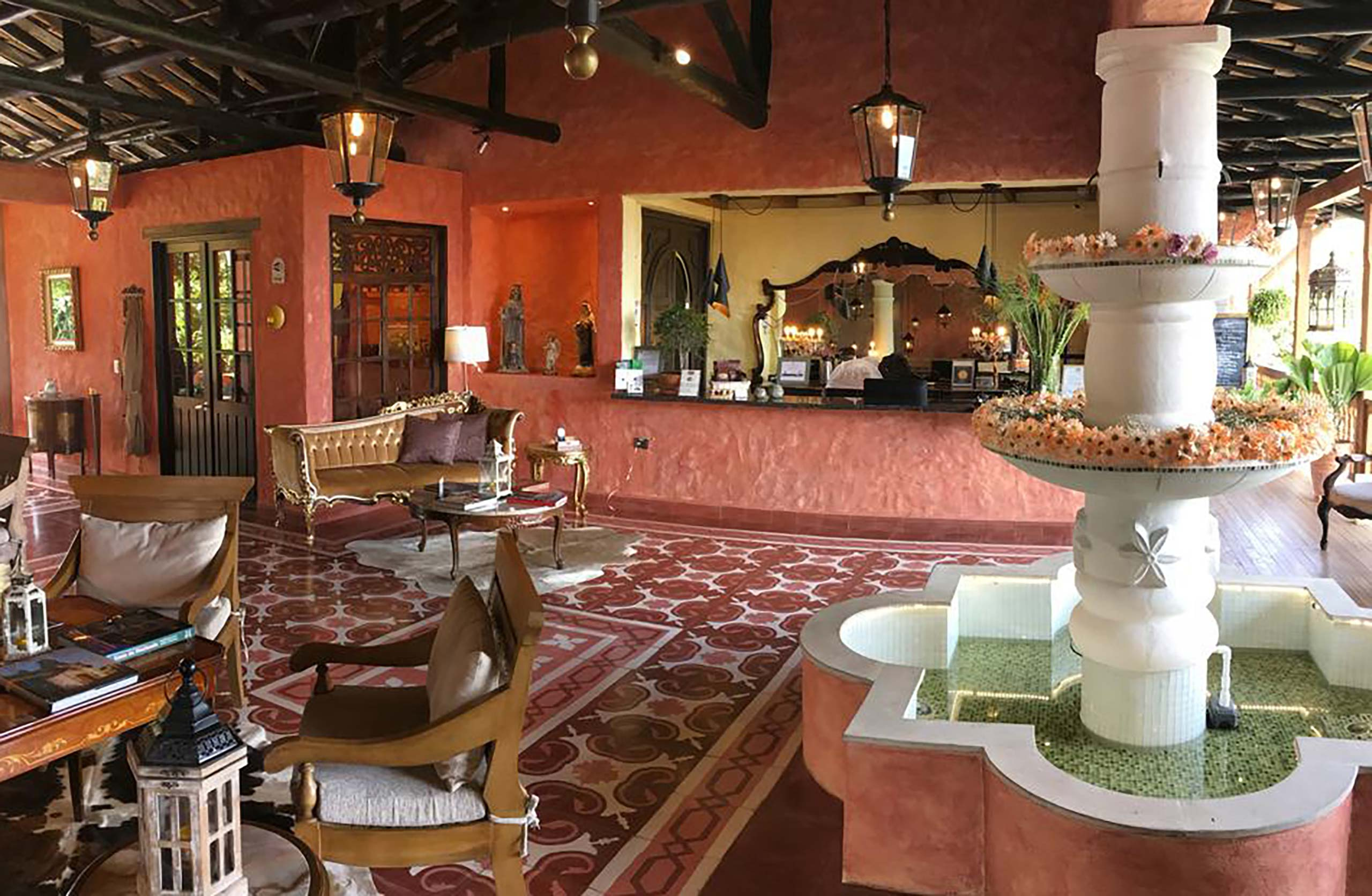 Reception desk in a pink room filled with couches and arm chairs. Off to the side is a large white fountain with water in it