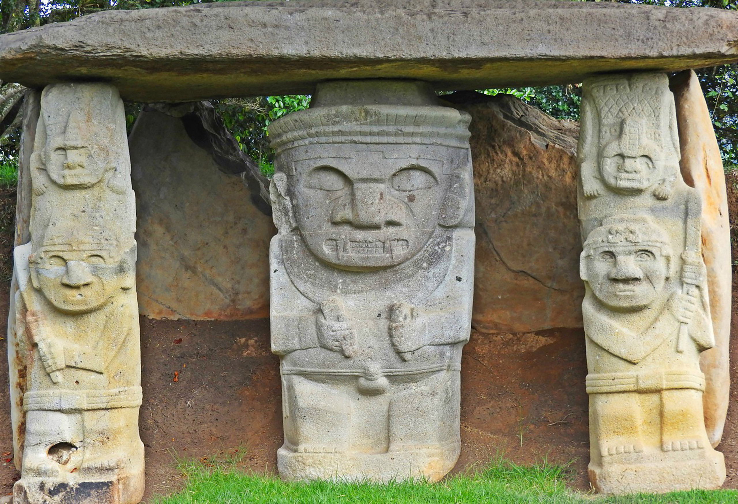 Three large statues guarding an ancient tomb. The middle of one man and the two outside statues with two faces