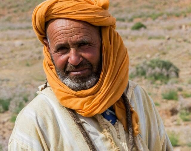 Bedouin man in the desert of Western Morocco with his head wrapped in yellow