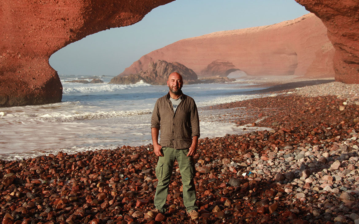 Man stands, hands in pocket, on a rocky beach with the ocean and wind shaped sand arches in the background.